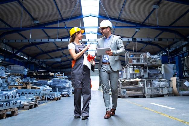 Gerente supervisor y trabajador industrial en uniforme caminando en la gran sala de la fábrica de metal y hablando de aumentar la producción