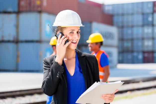 Gerente con teléfono hablando en el patio de envío