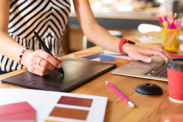 Gerente trabajando duro. cerca del administrador creativo diligente con reloj inteligente trabajando duro