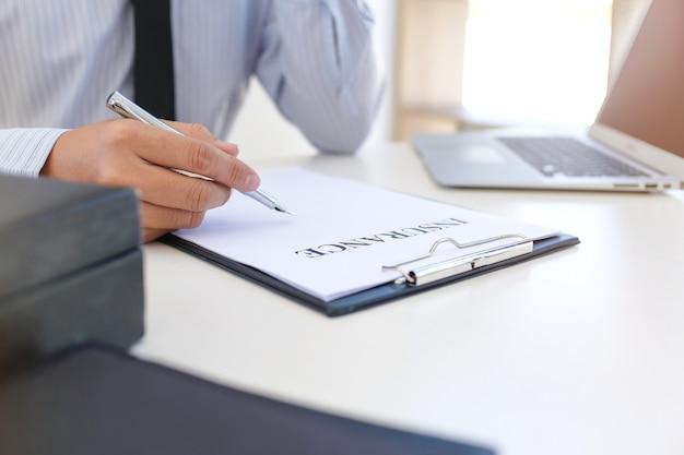Gerente de ventas dando asesoramiento en documento de formulario de solicitud, considerando oferta de préstamo hipotecario para seguros de automóvil y vivienda