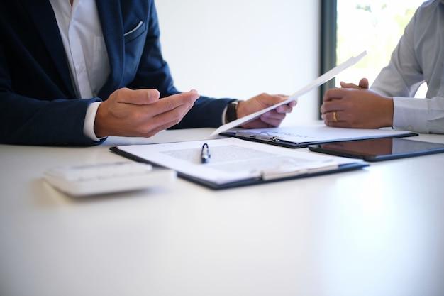 Gerente de ventas dando consejo formulario de solicitud de documento, teniendo en cuenta la oferta de préstamo hipotecario para el seguro de coche y casa.