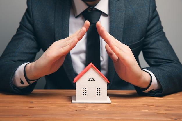 Gerente de ventas o agente inmobiliario con casa de muestra