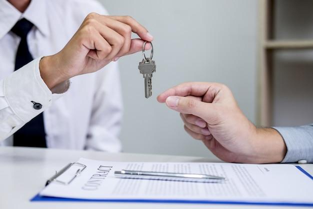 Gerente de ventas que entrega las llaves al cliente después de firmar el contrato de arrendamiento.