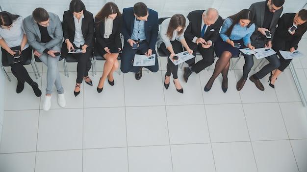 Gerente de vista superior discutiendo horarios comerciales con empleados de la empresa