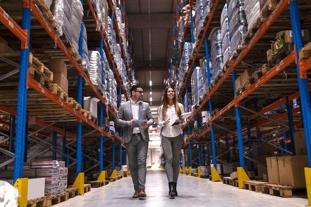 Los gerentes de almacén caminando por un gran centro de distribución