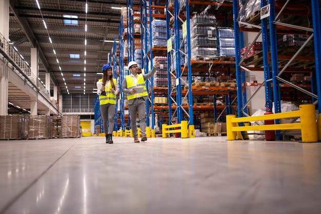 Los gerentes de almacén caminando en un gran departamento de almacenamiento controlando la distribución al mercado.