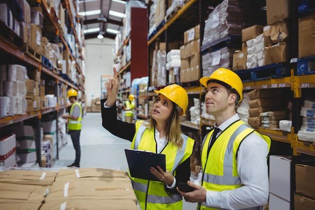 Gerentes de almacén mirando portapapeles con cascos