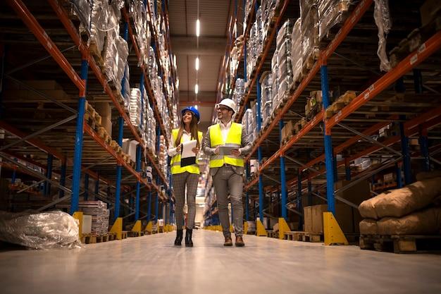 Gerentes caminando por un gran almacén controlando la distribución de mercancías.