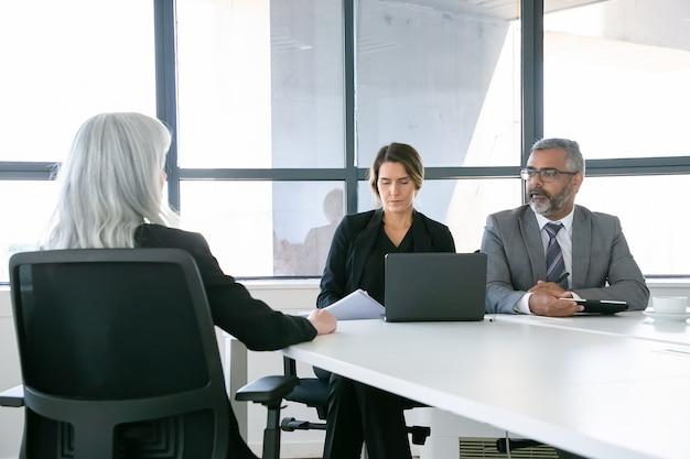 Gerentes de empresa serios hablando con candidato de trabajo en la entrevista. vista posterior, copie el espacio. concepto de empleo y carrera