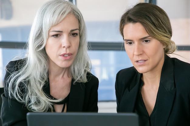 Gerentes de proyectos femeninos enfocados mirando la pantalla del portátil y hablando. vista frontal. concepto de comunicación y trabajo en equipo