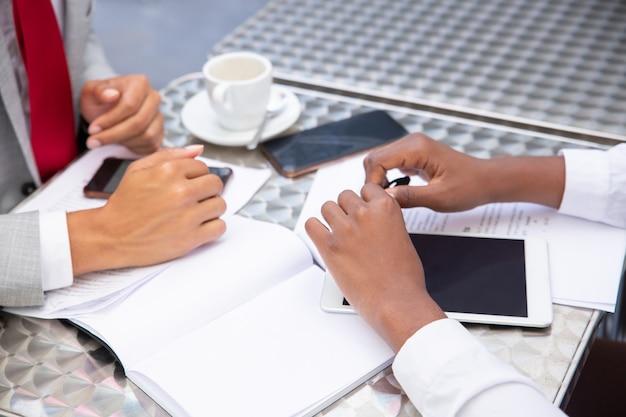 Gerentes sentados a la mesa con documentos y dispositivos digitales.