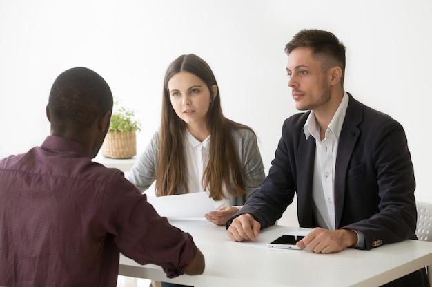 Los gerentes serios de recursos humanos escuchan al solicitante africano en una entrevista de trabajo