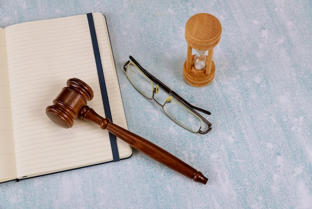 Gestión del tiempo reloj de arena con arena en una subasta de mazo de madera, libreta de gafas de lectura
