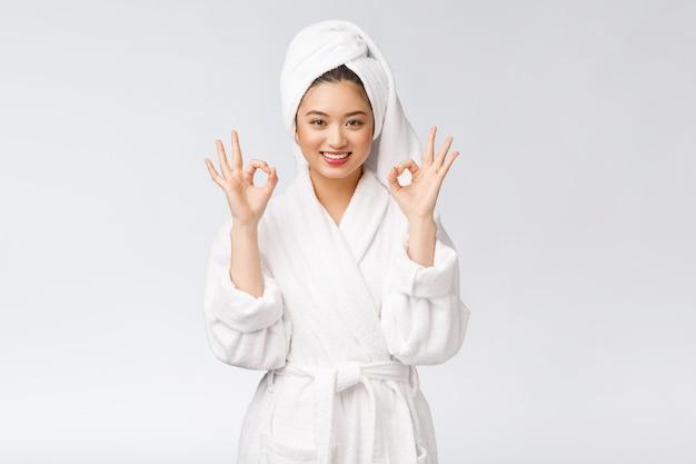 Gesto asiático de la mujer asiática de la belleza para el buen producto facial concepto aislado de la belleza y de la moda