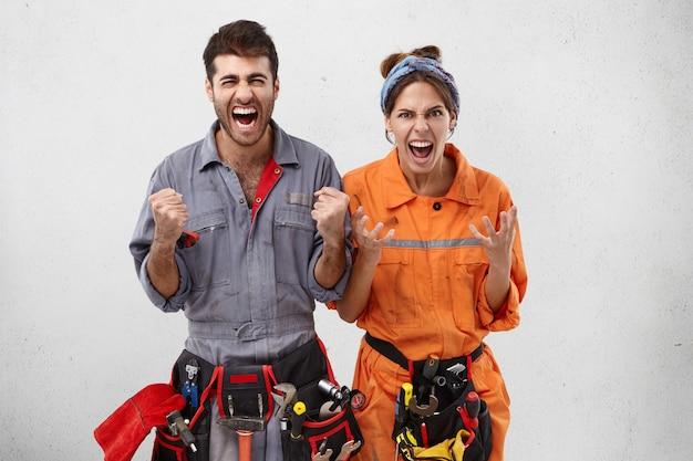 El gesto de los constructores masculinos y femeninos furiosos emocionales tiene expresiones irritadas ya que hay mucho trabajo