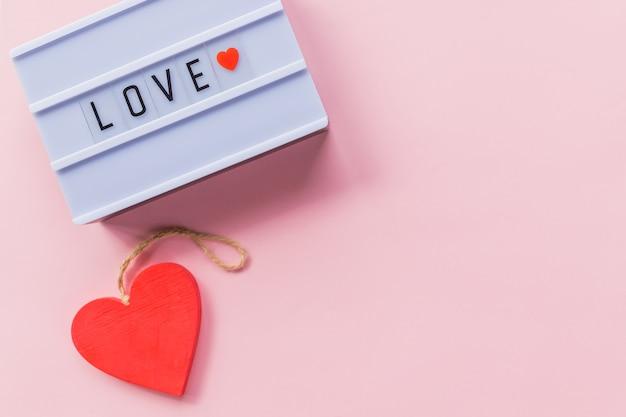 Gesto romántico, confesión de amor, feliz día de san valentín, letras de caja de luz, tarjeta de felicitación. corazón rojo sobre fondo rosa. copie el espacio. foto de una caja de luz con texto, amor.