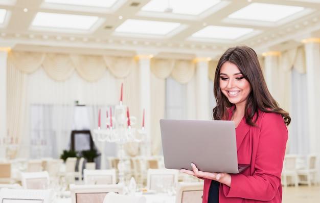 Gestor de eventos feliz usando laptop en salón de banquetes