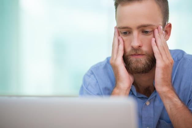 Gestor serio que se sienta en la computadora portátil en el estrés