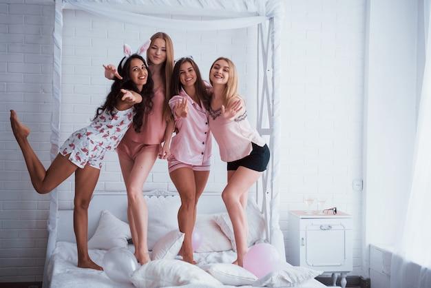 Gestos y saludos. de pie en el blanco de lujo malo en vacaciones con globos y orejas de conejo. cuatro hermosas chicas en ropa de noche tienen fiesta