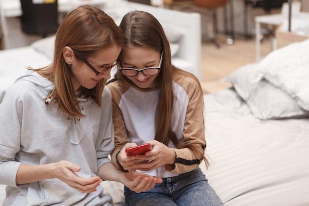 Giel adolescente mostrando algo en su teléfono inteligente a su mamá