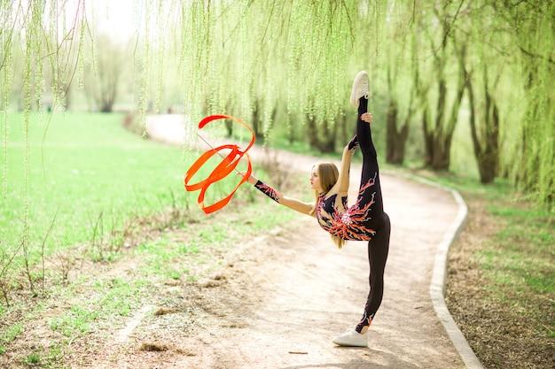 Gimnasia rítmica. joven gimnasta con cinta roja al aire libre en el parque