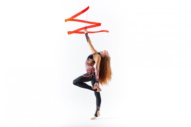 Gimnasia rítmica. joven gimnasta con cinta roja sobre blanco