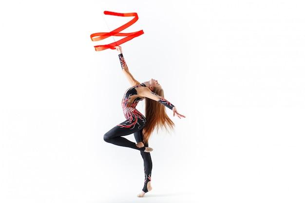 Gimnasia rítmica. joven gimnasta con cinta roja sobre fondo blanco.