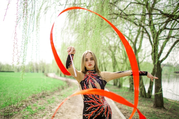 Gimnasia rítmica. joven gimnasta femenina con cinta roja al aire libre en el parque