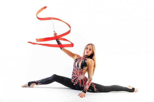 Gimnasia rítmica. joven gimnasta femenina con cinta roja sobre fondo blanco.