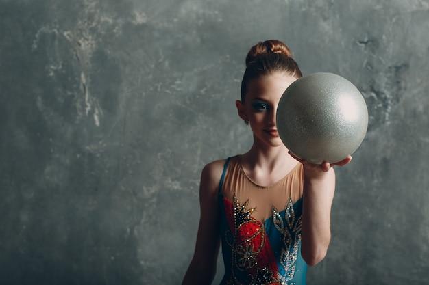 Gimnasia rítmica del retrato de la mujer del gimnasta profesional de la muchacha joven con la bola en el estudio.