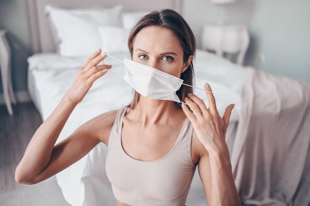Gimnasio en casa. young fit mujer delgada en mascarilla de protección haciendo ejercicios de yoga por la mañana en el dormitorio