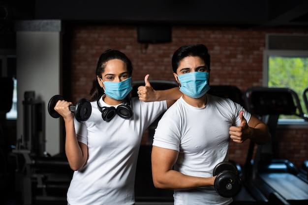 Gimnasio después de la corona: joven pareja india que hace ejercicio en el gimnasio después del brote de corona y usa una mascarilla protectora