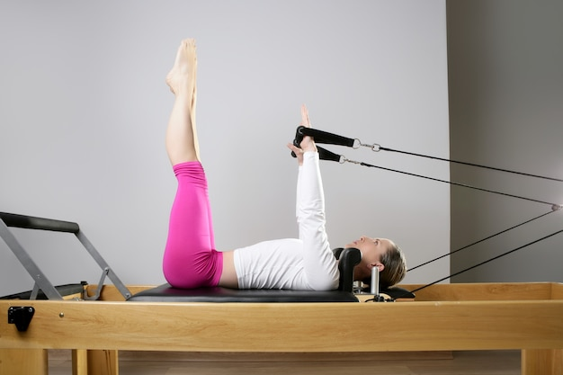 Gimnasio mujer pilates estirando deporte en cama reformer