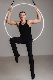 Gimnasta aéreo masculino realiza elemento acrobático en el ring.