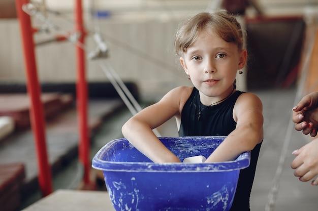Gimnasta chica en apretones de mano de gimnasia manchando tiza de gimnasio. niño en una escuela de atletismo.