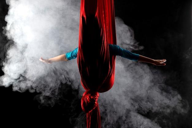 Gimnasta chica no identificada escondida en cintas aéreas rojas rodeadas de humo