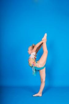 Una gimnasta chica rubia se encuentra de lado en una postura gimnástica sobre una pared azul aislada