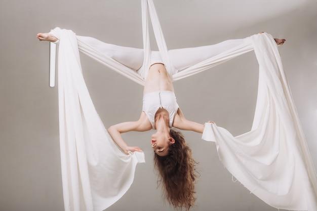 Gimnasta femenina haciendo acrobacias aéreas de seda.