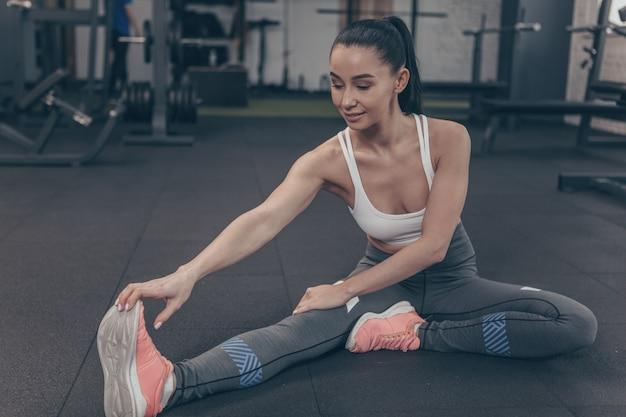 Gimnasta femenina hermosa que estira sus piernas en el estudio del gimnasio, copie el espacio.