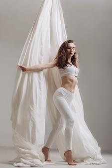 Gimnasta femenina posando con cintas de seda aéreas