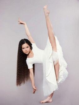 Una gimnasta hermosa, joven y en forma realiza un elemento de gimnasia rítmica.