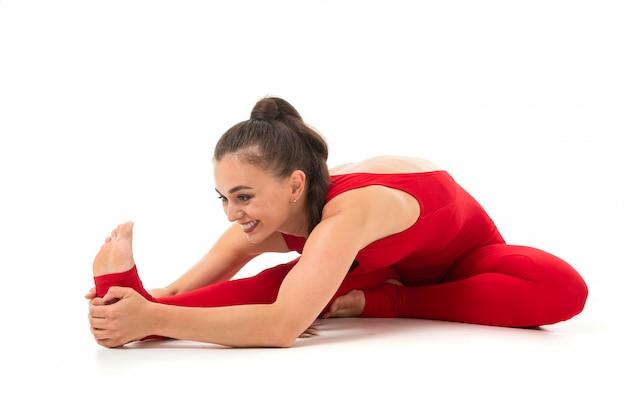 Una gimnasta joven y bella con el pelo largo y oscuro relleno en una cola de caballo con un traje elástico deportivo rojo calienta y estira los músculos.
