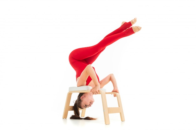 Una gimnasta joven y bella con el pelo largo y oscuro relleno en una cola de caballo con un traje elástico deportivo rojo realiza una