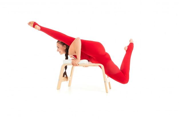 Una gimnasta joven y bella con el pelo largo y oscuro relleno en una cola de caballo en un traje elástico deportivo rojo se sienta en una cuerda