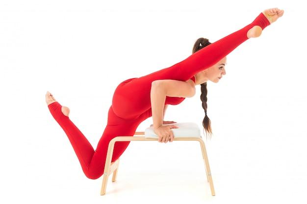 Una gimnasta joven y bella con el pelo largo y oscuro relleno en una cola de caballo en un traje elástico deportivo rojo se sienta en un hilo y se para en una mano.