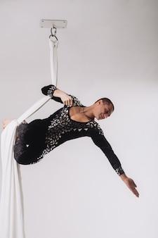 Gimnasta masculino haciendo acrobacias aéreas de seda.