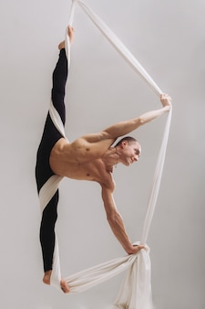 Gimnasta masculino haciendo la división con cintas de seda aéreas.