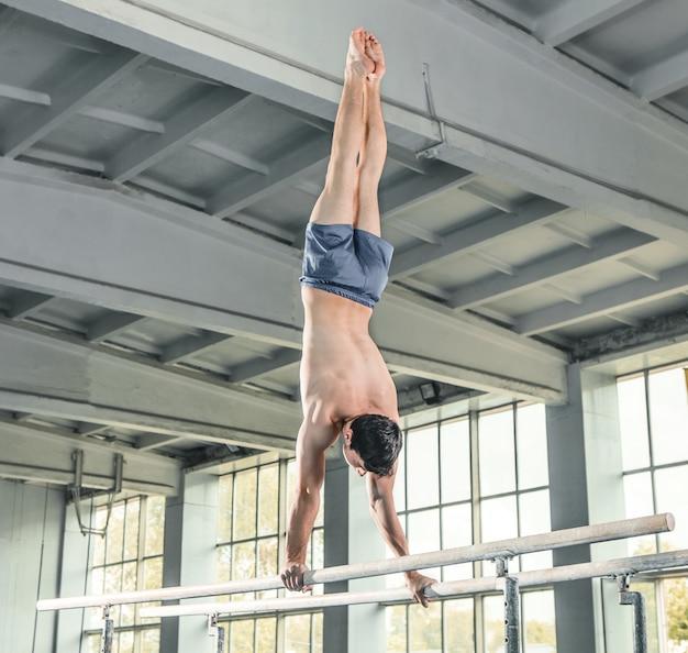 Gimnasta masculino realizando parada de manos en barras paralelas