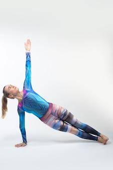 Gimnasta en medias multicolores durante el estiramiento