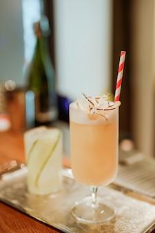 Gin tonic con cóctel de pepino y piña colada en bandeja de plata. foto con poca profundidad de campo. imagen de estilo de vida vertical.